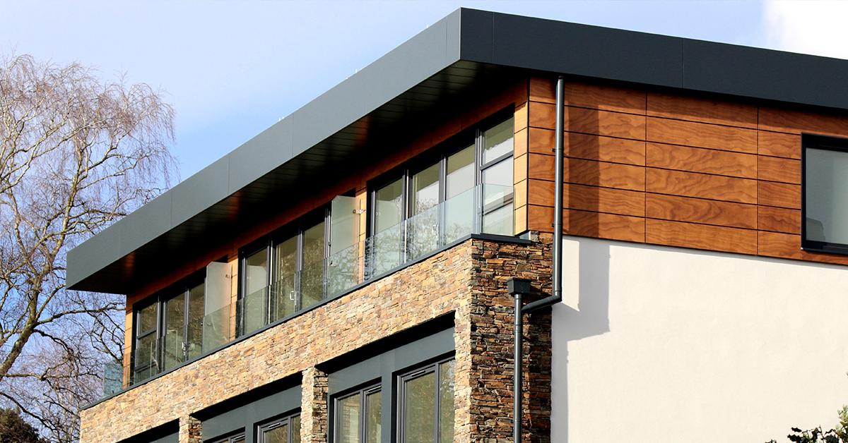 nizkoenergeticky montovany drevodom s drevenou oblohou kamennym obkladom a ciernymi oknami a dverami