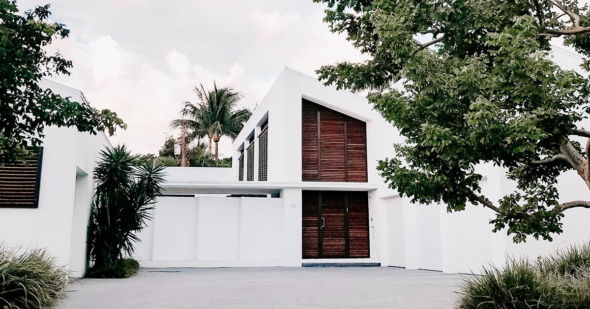 moderny drevodom biely s drevenymi dverami a stromami okolo